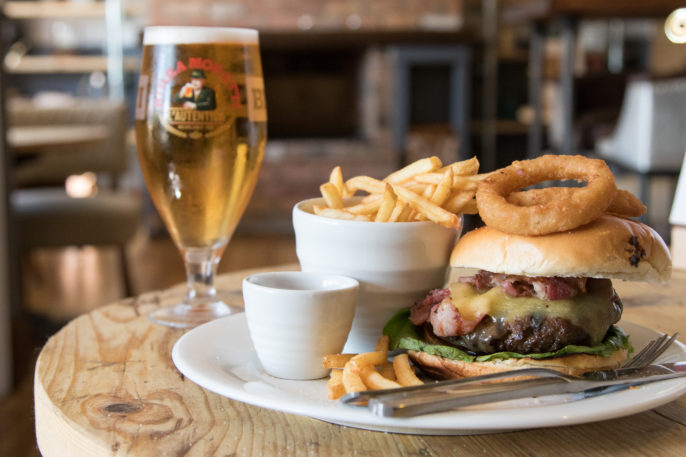 Double-stacked burger and long french fries served in a pub